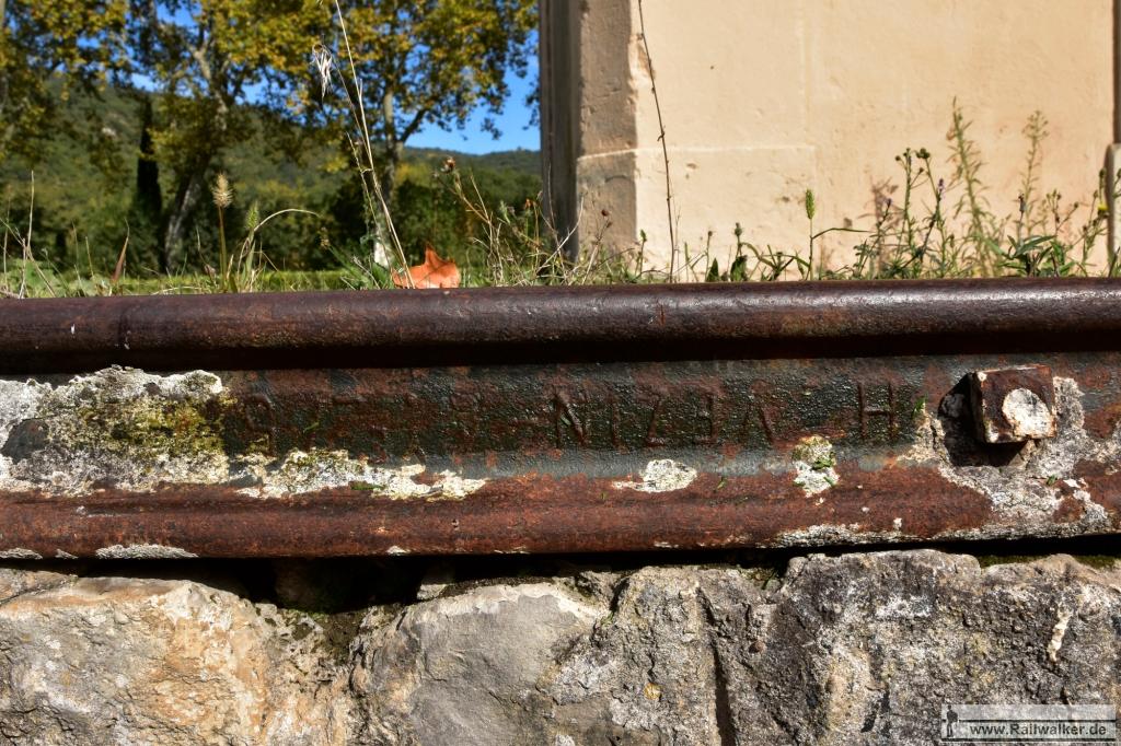 Am Bahnhof Im Bahnhof Alet-les-Bains. liegt an der Laderampe eine Schiene mit dem Walzzeichen einer belgischen Firma. Die Schiene stammt aus den 1870er Jahren.
